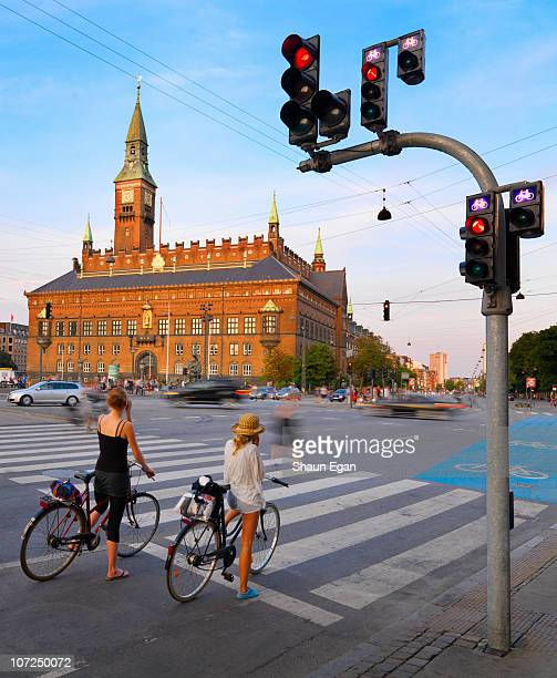 two woman on bikes in-front of town hall - copenhagen stock pictures, royalty-free photos & images