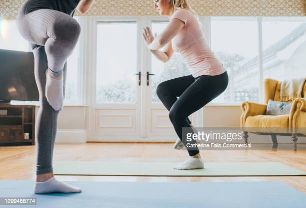 two woman perform yoga in a home environment - human joint stock pictures, royalty-free photos & images
