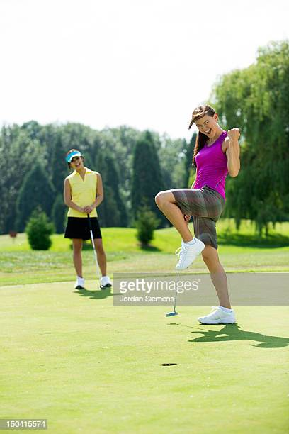 Two woman playing a game of golf.