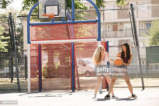 Two woman practising on basketball court