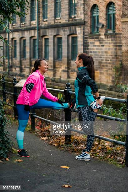Two Woman Prepare To Run By Stretching
