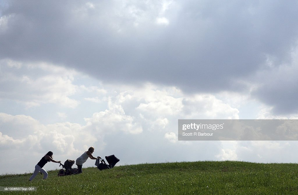 Two woman push Baby Carriages up a hill in Primrose Hill, London, England. : Foto stock