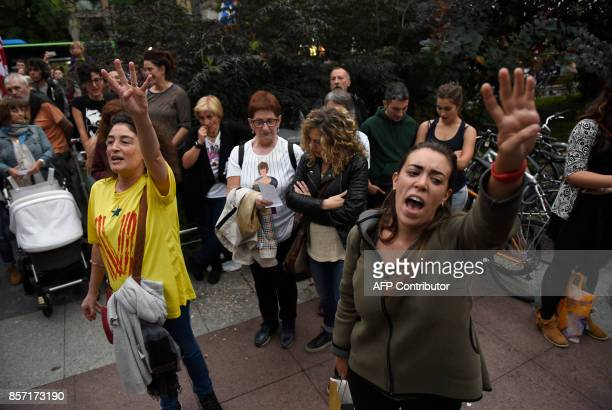 Two woman raise their hand while people sing Els Segadors the national anthem of Catalonia during a demonstration called by Basque unions supporting...