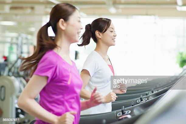 Two woman running on treadmill in gym