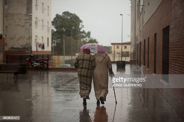 Two woman shelter under an umbrella as they walk in El Principe district of Ceuta on December 3 2014 AFP PHOTO/ JORGE GUERRERO