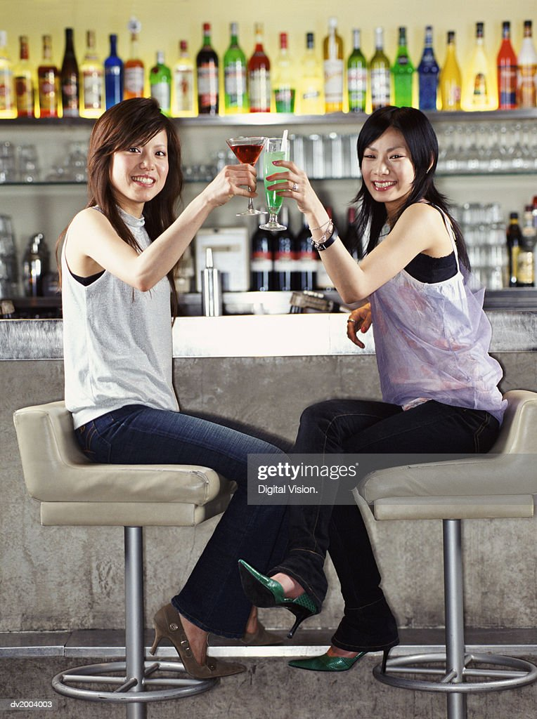 Two Woman Sitting at a Bar Making a Toast With a Cocktail : Stock Photo