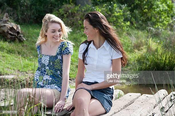 Two woman sitting on wooden bridge