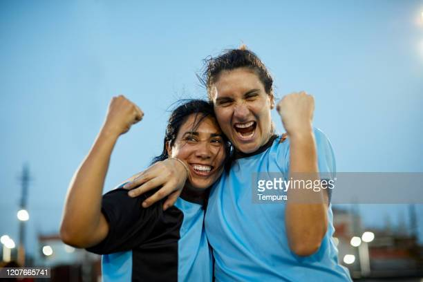 two woman soccer players rising fists in celebration. - soccer competition stock pictures, royalty-free photos & images
