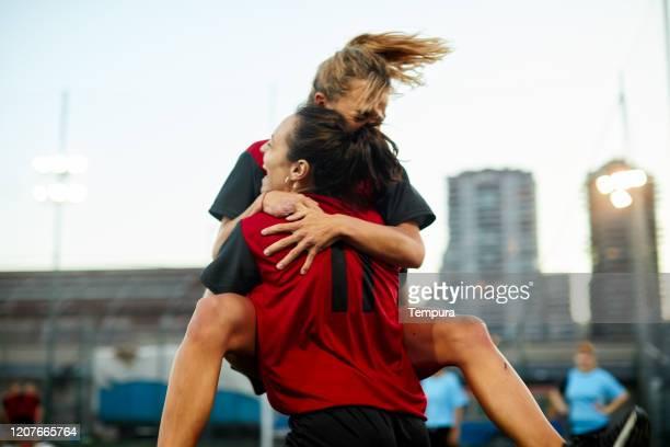 dos compañeras de equipo de fútbol se abrazan después de marcar un gol en la celebración. - feminidad fotografías e imágenes de stock