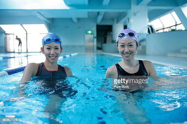 Two woman standing in the swimming pool