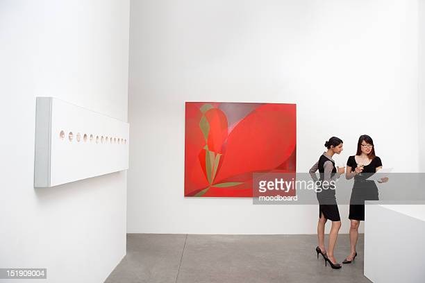 Two woman standing next to wall paintings