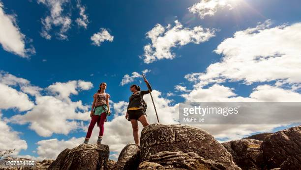 two woman standing on top of a cliff in chapada dos veadeiros national park, goias, brazil - parco nazionale di chapada diamantina foto e immagini stock