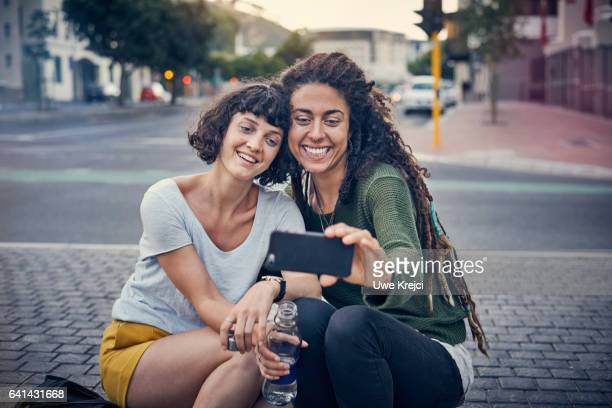 Two woman taking self portrait in the city