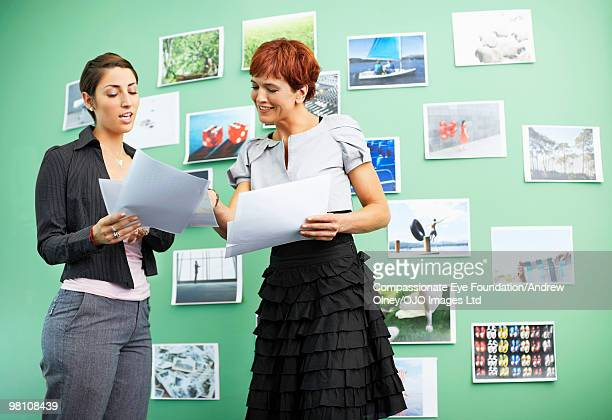 two woman talking to each other with paperwork - up the skirt pics stock pictures, royalty-free photos & images