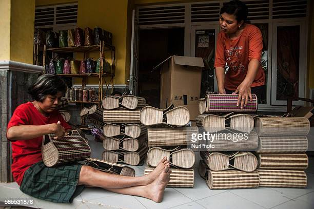 Two woman tidy up handicraft weaving in Gemplong Yogyakarta Indonesia on Auguts 3 2016 The weaving craft can be made tablecloths bags and slippers...