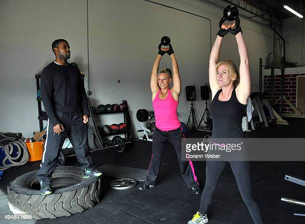 Two woman use kettlebell weights as trainer looks on