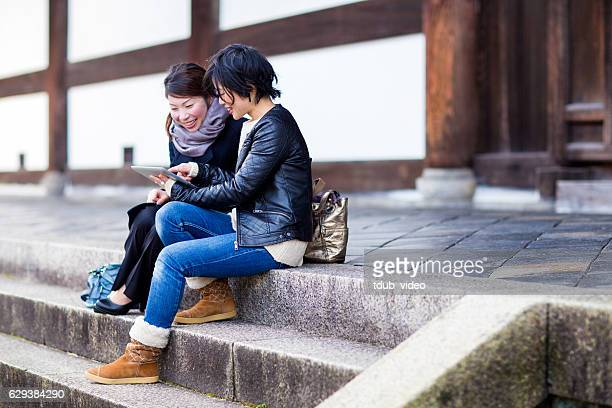 two woman using a digital tablet at a japanese temple - tdub_video stock pictures, royalty-free photos & images