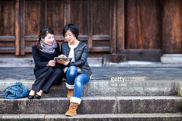 Two woman using a digital tablet at a Japanese temple