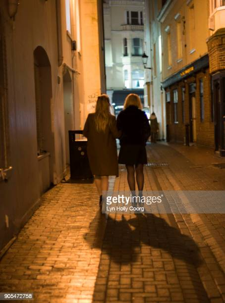 two woman walking in alleyway at night - lyn holly coorg stock photos and pictures