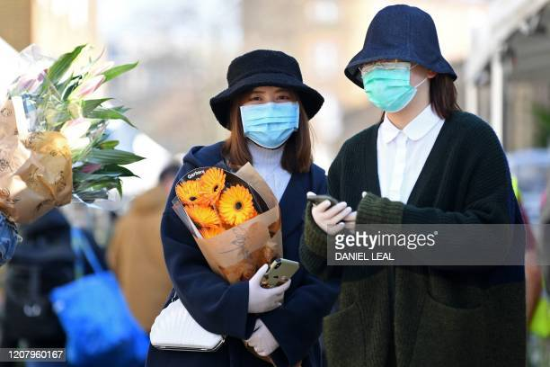 Two woman wear protective faces masks during a visit to Columbia Road flower market in east London on Mother's Day March 22 2020 Up to 15 million...