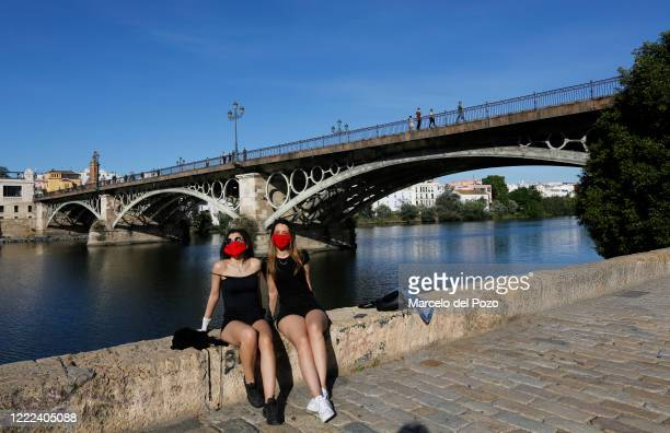 Two woman wearing protective mask sunbathe on the riverside of the Guadalquivir on May 02 2020 in Seville Spain Spain continues to ease the Covid19...