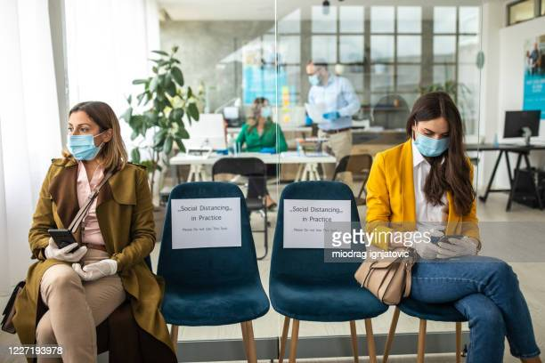 two woman with protective face mask and surgical gloves in bank waiting room - waiting room stock pictures, royalty-free photos & images