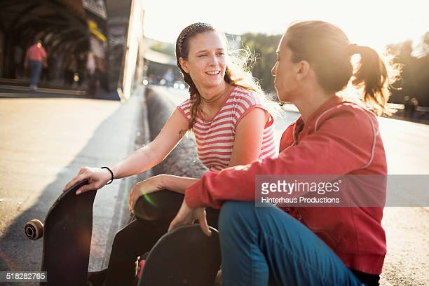 Two Woman with Skateboards Chatting