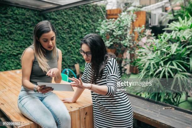 two woman working together outdoors at desk - fundador imagens e fotografias de stock