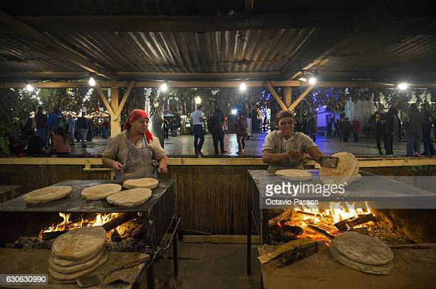 Two womans cooks the Bolo de Caco, which is a shard wheat bread typical of the region of Madeira Island, on December 29, 2016 in Funchal, Madeira,...