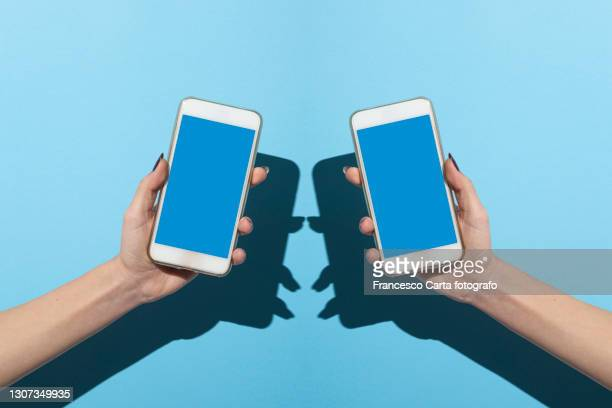 two woman's hands holding smartphone - tempio pausania stock pictures, royalty-free photos & images