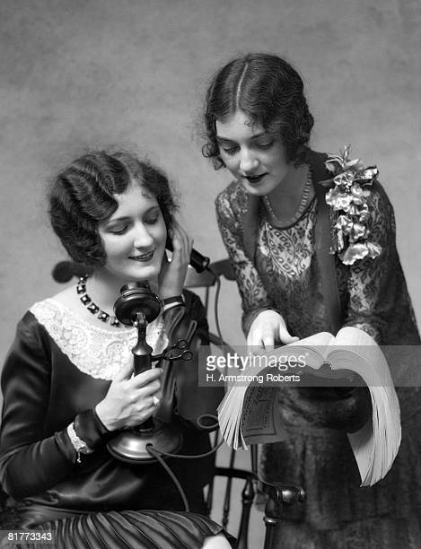 Two Women 1 Is On The Phone The Other Is Showing Her A Number In The Phone Directory Both Are Wearing Dressey Dresses Smiling White & Black Lace.