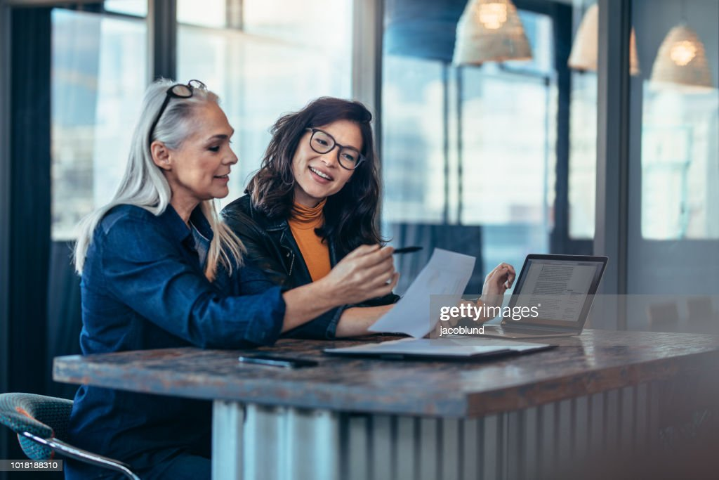 Two women analyzing documents at office : Stock Photo