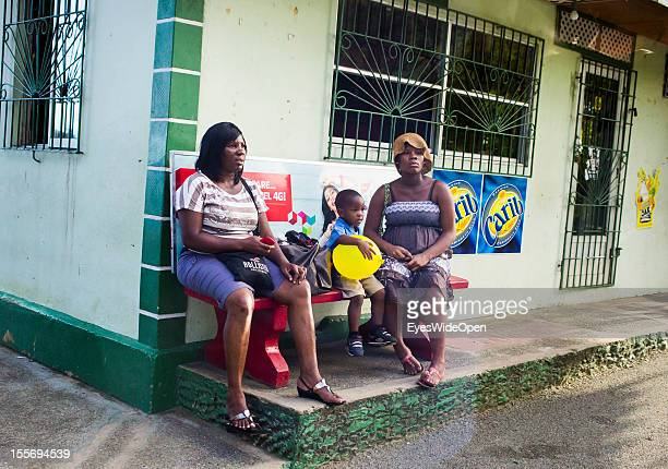Two women and a child waiting in front of a shop on October 21 2012 in Scarborough Trinidad And Tobago
