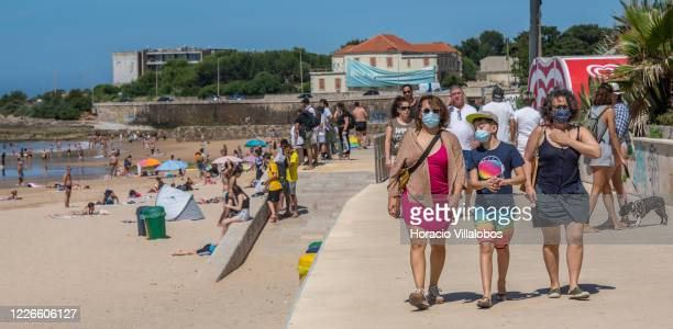 Two women and a child wear a protective masks while walking on the promenade on Carcavelos Beach near Lisbon during the COVID19 Coronavirus pandemic...