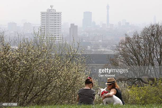 Two women and a dog sit on Parliament Hill in Hampstead Heath overlooking an overcast Central London on April 10 2015 in London England Air pollution...