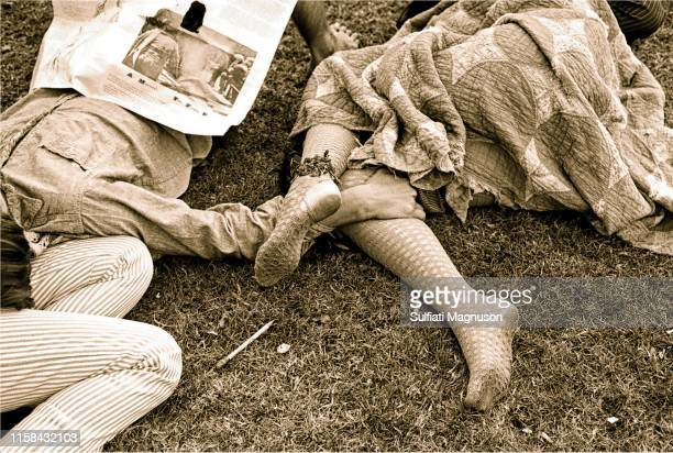 Two women and a man arms and legs linked, lying on the grass at the 1st Elysian Park Love-In on March 26, 1967 in Los Angeles, California.