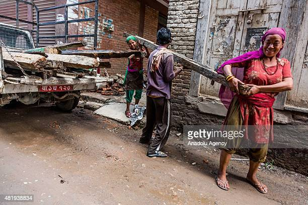 Two women and a man carry a large piece of wood belonging to a destroyed building in Kathmandu on July 25, 2015. Today marks the 3 month anniversary...
