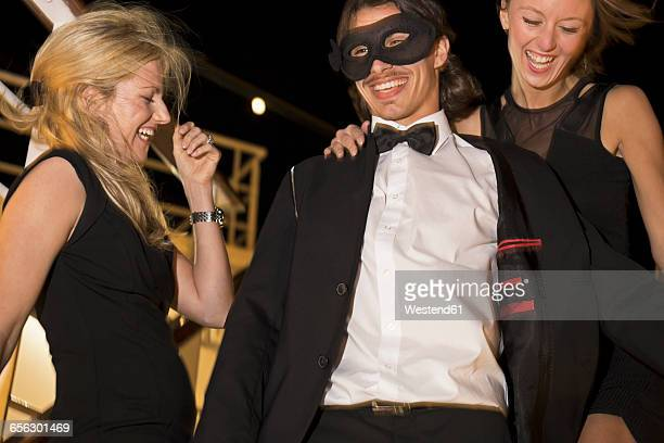Two women and a man laughing and dancing on a cruise liner at night