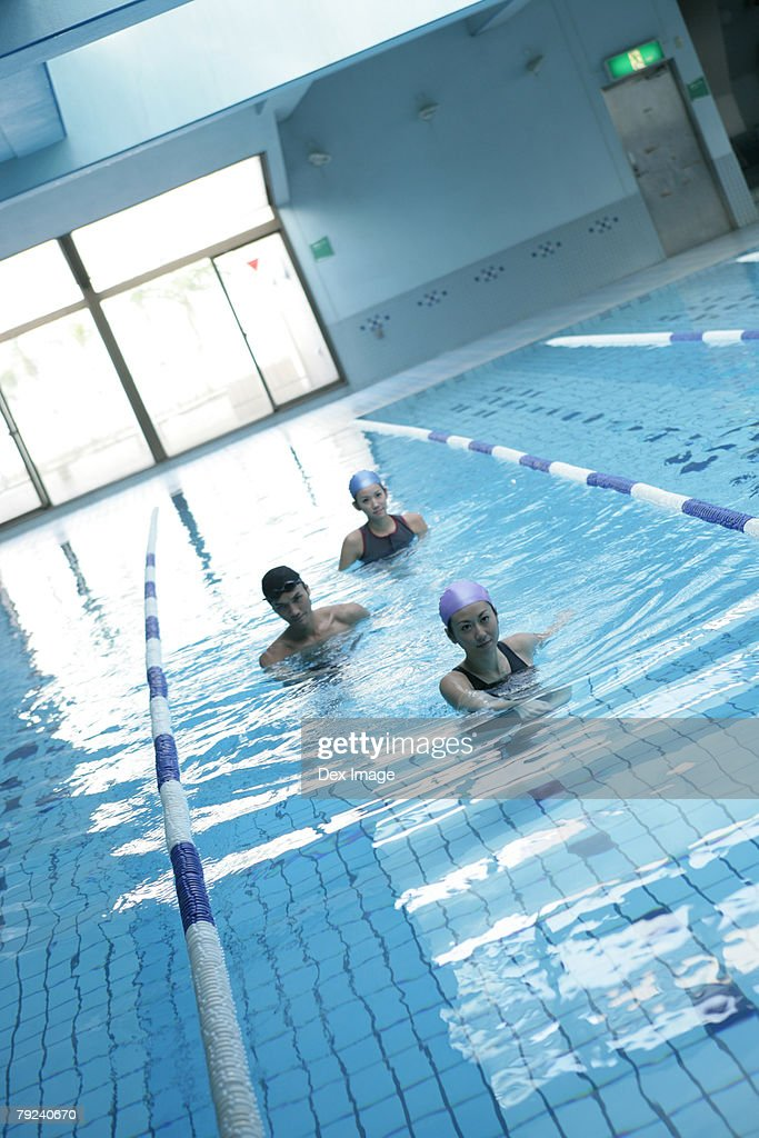 Two women and a man standing in the swimming pool : Stock Photo