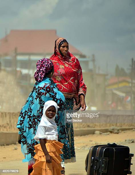Two women and a small girl, dressed in colorful outfits await the bus in a busy shopping area outside of Dar es Salaam, Tanzania.