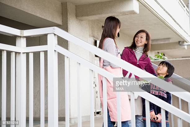Two women and boy chatting at steps