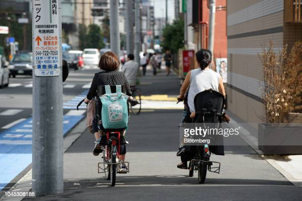 Two women and children ride on bicycles along a sidewalk in Kawasaki Kanagawa Prefecture Japan on Tuesday Sept 18 2018 Japan's population of 127...