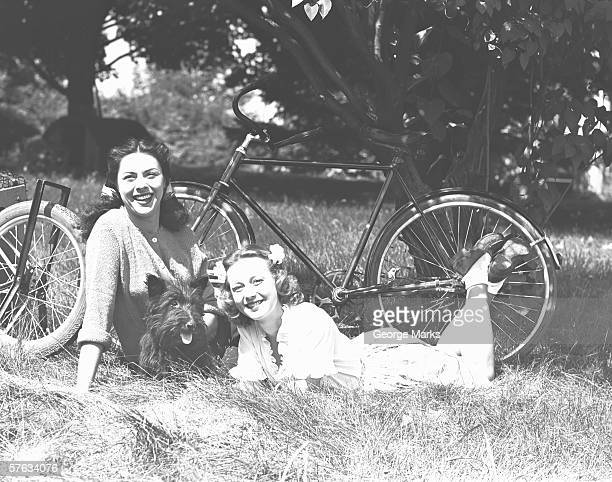 Two women and dog resting on grass, (B&W)