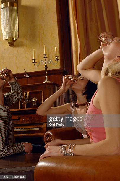 Two women and man in armchairs drinking shots