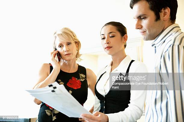 """two women and one man looking at document - """"compassionate eye"""" fotografías e imágenes de stock"""