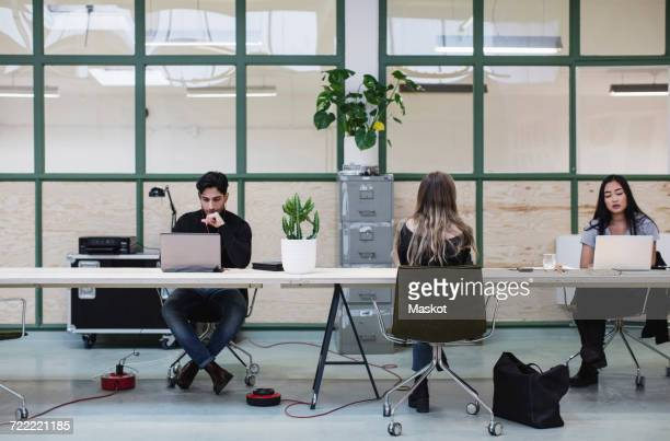 Two women and one man working at desk in creative office