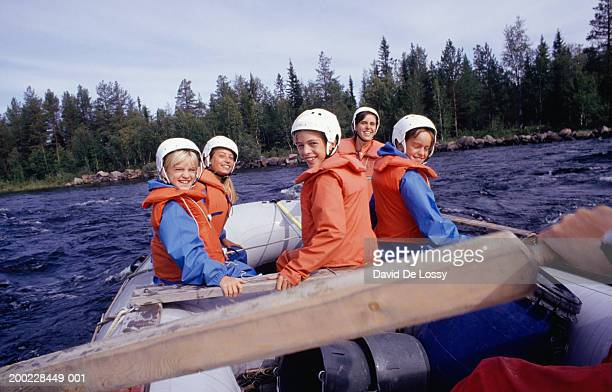 Two women and three girls (8-9) (13-14) in raft on river