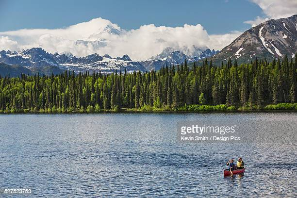 two women and young girl in a red canoe on byers lake with green forested shoreline and mount mckinley peaking through the clouds, denali state park - state park stock pictures, royalty-free photos & images