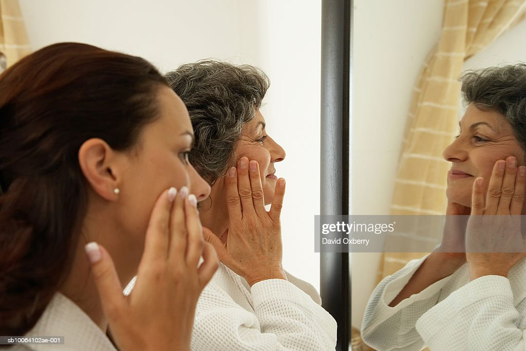 Two women applying cream, looking in mirror, profile : Stock Photo
