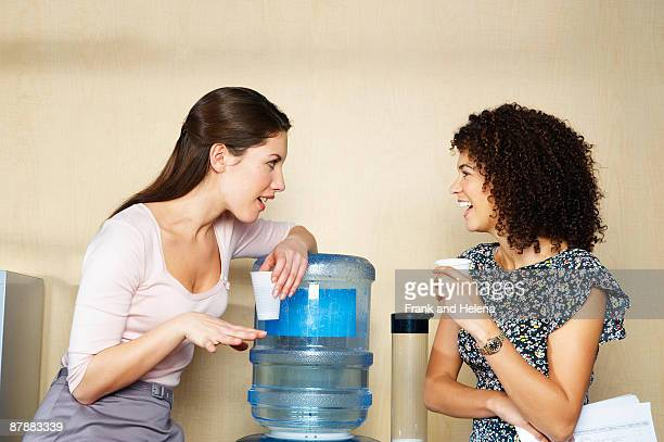 Two women are chatting by water cooler